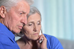 Woman holding hand on cheek. Portrait of sad senior couple, women holding hand on cheek with toothache Stock Photography