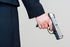 Woman holding hand gun on white background Stock Photography