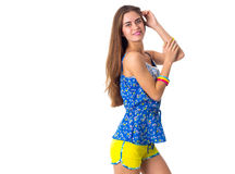 Woman holding hand on her head. Young attractive woman in blue T-shirt and yellow shorts standing sidewise and holding hand on her head on white background in Royalty Free Stock Image