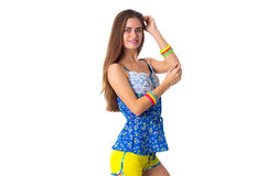 Woman holding hand on her head. Young beautiful woman in yellow shorts and blue T-shirt standing sidewise and holding hand on her head on white background in Stock Photography