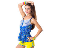 Woman holding hand on her head. Young beautiful woman in yellow shorts and blue T-shirt holding hand on her head on white background in studio Stock Photography