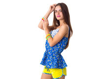 Woman holding hand on her head. Young smiling woman in blue T-shirt and yellow shorts standing sidewise and holding hand on her head on white background in Royalty Free Stock Photo