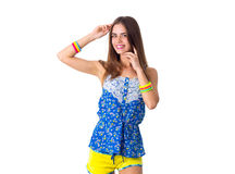 Woman holding hand on her head. Young smiling woman in blue T-shirt and yellow shorts with varicoloured bracelets holding hand on her head on white background in Stock Photography