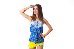 Woman holding hand on her head. Young smiling woman in blue T-shirt and yellow shorts holding hand on her head on white background in studio Stock Images