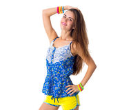 Woman holding hand on her head. Young smiling woman in yellow shorts and blue T-shirt holding hand on her head on white background in studio Royalty Free Stock Photo