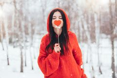 Woman holding in hand red heart for Valentines Day on winter background stock image
