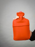 Woman holds hot water bottle in red fleece cover Stock Photography