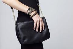 Woman holding handbag, focus on the handbag Royalty Free Stock Photography