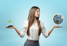 Woman Holding Handful Of Soil With Plant In One Hand And Globe In The Other Royalty Free Stock Photography