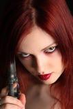 Woman holding a handgun. Closeup of a young redhead woman holding a gun stock photos