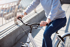Woman holding handles on bicycle Stock Images