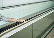 Woman holding on handrail when ascending escalator stock photos