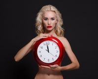 Woman holding in hands big red clock. Stock Photos