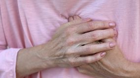 Woman holding hands on chest, sudden heart attack, health problem, emergency. Stock photo stock image