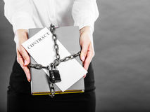 Woman holding in hands contract and chain with padlock Royalty Free Stock Photos