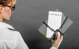 Woman holding in hands contract and chain with padlock Royalty Free Stock Images