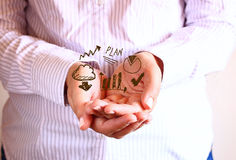 Woman holding hands in cupped shape and drawing of charts and infographics. close up image with selective focus Stock Photos
