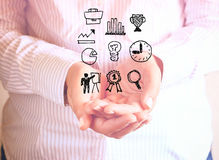 Woman holding hands in cupped shape and drawings of charts and infographics. Close up image with selective focus. Business concept royalty free stock photography