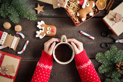 Woman holding in hands hot christmas tea with candy cane against decorations, gift boxes, ribbon and ginger bread on wooden board. Royalty Free Stock Photography