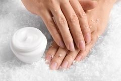 Woman holding hands near jar of cream on decorative snow. Winter skin care cosmetic stock images