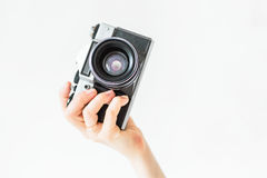 Woman holding in hands old vintage camera. Girl photographer and film camera Royalty Free Stock Photography