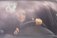 Woman holding hands on steering wheel front view. Picture of yang and beautiful driving woman. Girl holding hands on the steering wheel front view Royalty Free Stock Photography