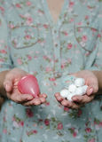 Woman holding in hands tampons and menstrual cup Stock Images