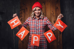 Woman holding happy letters red flags, christmas theme Royalty Free Stock Photos