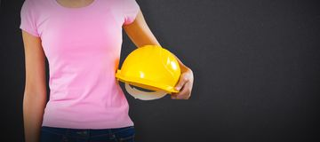 Composite image of woman holding hard hat against grey background. Woman holding hard hat against grey background against black chalkboard stock image