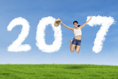Woman holding hat and leaping with number 2017 Stock Image