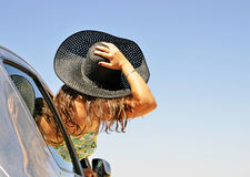 Woman holding hat peeking through the car window Stock Photography