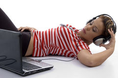 Woman holding headphone and looking at laptop Stock Image
