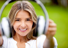 Woman holding headphones Stock Images
