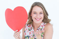 Woman holding heart card and blowing kiss Stock Images