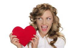 Woman holding heart next to him and looks away Royalty Free Stock Image
