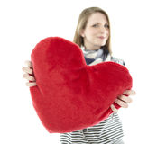 Woman holding heart pillow Stock Image