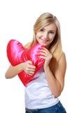 Woman holding heart pillow Stock Photos
