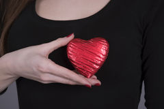 Woman holding a heart shape against her body. Young woman holding a heart shape chocolate against her chest Stock Photography
