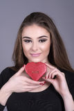 Woman holding a heart shape box. Young woman holding a heart shape chocolate box inscribed with the word love Royalty Free Stock Images