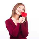 Woman holding heart shape and dreaming. Studio shot of young caucasian smiling woman isolated on white background, holding heart shape and dreaming Royalty Free Stock Photography