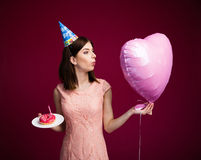 Woman holding heart shaped balloon and cake with candle. Over pink background. Blowing on balloon Royalty Free Stock Photography