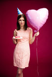 Woman holding heart shaped balloon and donut with candle Stock Photo