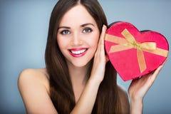Woman holding heart-shaped box Stock Photography