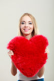 Woman holding heart shaped pillow love symbol. Valentines day love and relationships concept. Blonde long hair young woman holding heart shaped pillow love stock photos