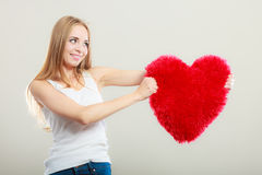 Woman holding heart shaped pillow love symbol Royalty Free Stock Images