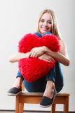 Woman holding heart shaped pillow love symbol Royalty Free Stock Photo