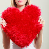 Woman holding heart shaped pillow love symbol. Valentines day love and relationships concept. Blonde long hair young woman holding heart shaped pillow love stock photography