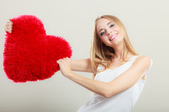 Woman holding heart shaped pillow love symbol Royalty Free Stock Photos