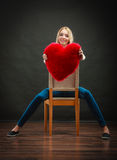 Woman holding heart shaped pillow love symbol. Valentines day love and relationships concept. Blonde long hair young woman holding heart shaped pillow love royalty free stock image