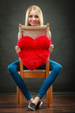 Woman holding heart shaped pillow love symbol. Valentines day love and relationships concept. Blonde long hair young woman holding heart shaped pillow love royalty free stock photography